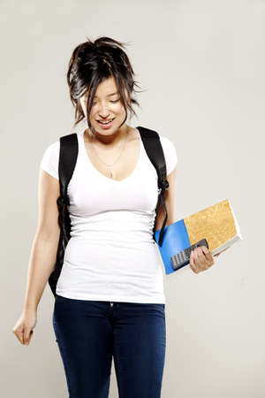 Young asian student holding textbooks and smiling for camera photo
