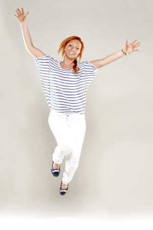 red head woman: Red head woman very happy jumping in studio