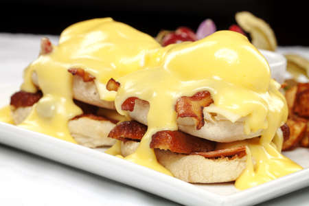 Double stacked eggs benedict with bacon and hollandaise sauce photo
