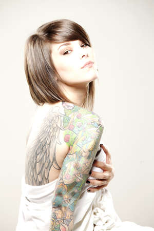 Girl with tattoos wrapped in sheet   Stock Photo