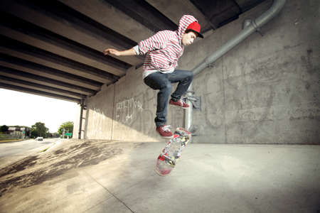 maneuver: Skateboarder under overpass flipping his board