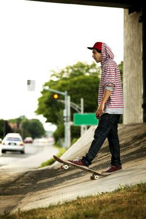 maneuver: Skateboarder under overpass flipping his board