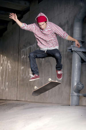 Skateboarder under overpass flipping his board photo