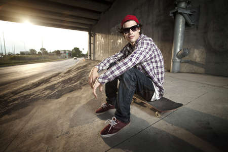 Skateboarder under overpass relaxing with style