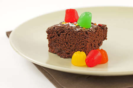 Brownies topped with candies of assorted colors on plate photo