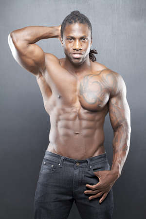 Black fitness model in jeans with no shirt flexing muscles photo