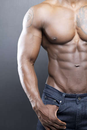 haitian: Black fitness model in jeans with no shirt flexing muscles