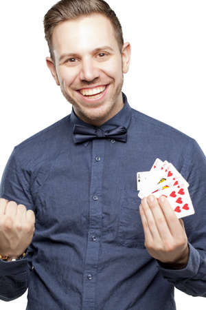Hipster man in bow tie looking stylish playing poker holding royal flush photo