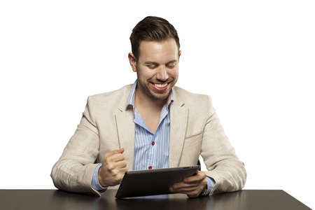 Young man in blazer looking confident playing on tablet against white background