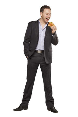 eating pizza: Young man in black suit eating pizza against white background