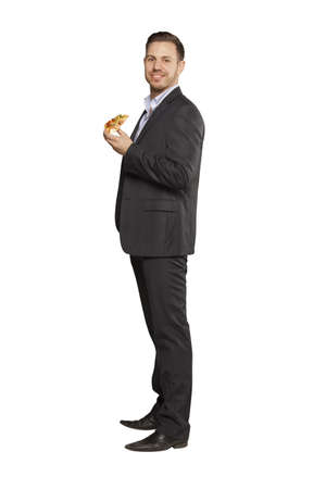 Young man in black suit eating pizza against white background photo