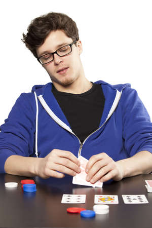 Young man playing poker at table photo