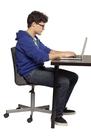 sitting on: Student sitting at table using computer relaxed