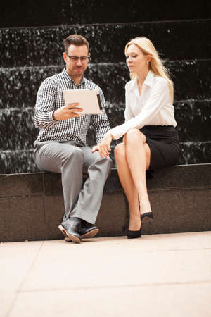 sector: Young business team sitting down together with waterfall behind using tablet