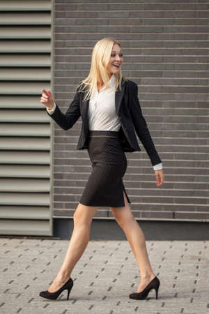 sector: Young professional in business attire projecting confidence against brick wall Stock Photo
