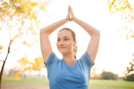 Young woman performing yoga positions in park during autumn photo
