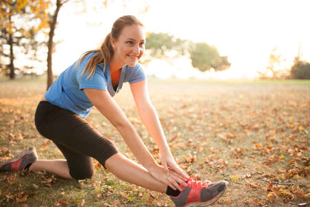 Young woman performing yoga positions in park during autumn Stock Photo