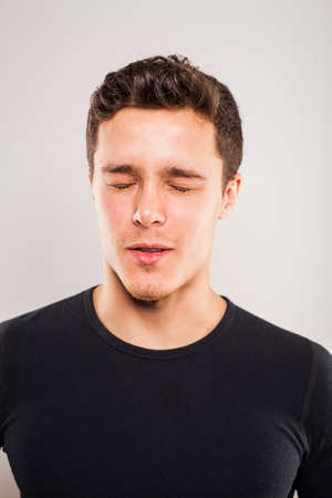 swagger: Portrait of young man with black shirt with eyes closed in studio setting Stock Photo