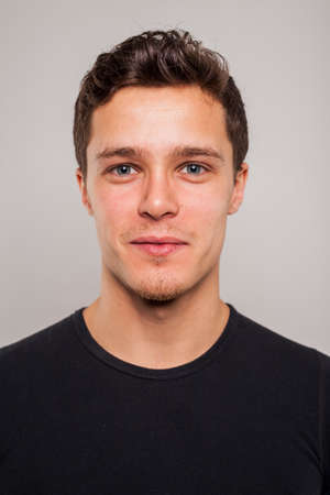 swagger: Portrait of young man with black shirt in studio setting Stock Photo