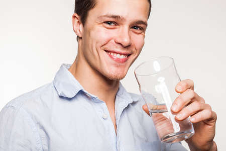 man drinking water: Young man drinking water in studio setting