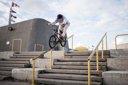 Bmx rider grinding on handrail in urban area, Montreal, Quebec, Canada