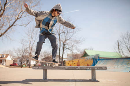 enthusiast: Young skateboard enthusiast in skatepark doing a nose grind