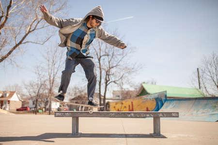 grind: Young skateboard enthusiast in skatepark doing a nose grind