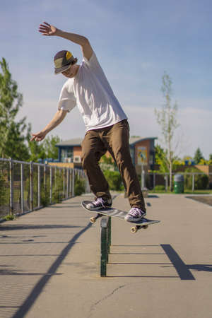 Feeble gring on rail in concrete skate park during summer Stock Photo