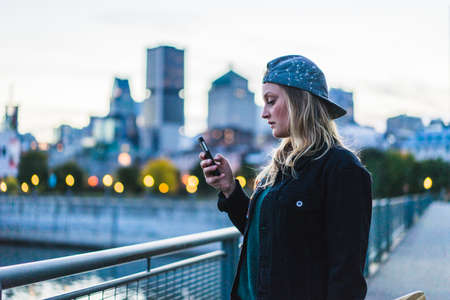 independance: Portrait of young teenage girl texting on her smartphone, Montreal, Quebec, Canada