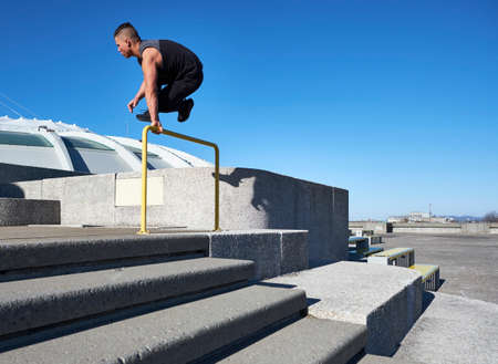Young male athlete jumping over hurdle in concrete park, Montreal, quebec, Canada Stock Photo