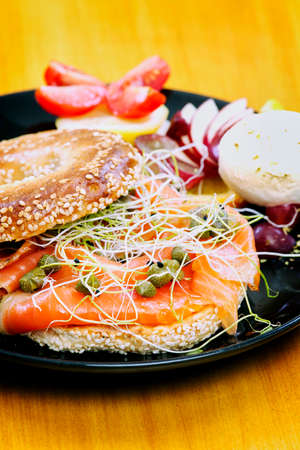 Smoked Salmon Sandwich on bagel with cream cheese and fruits Foto de archivo