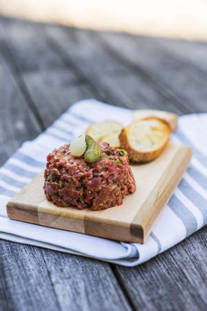 Beef tartare with pickle and crouton served on wood cutting board and cloth