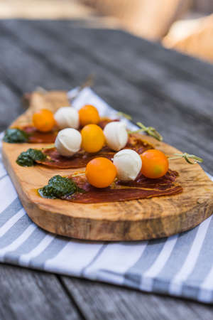 Bocconcini skewers with tomato on prosciuto and pesto on outdoor table Stock Photo