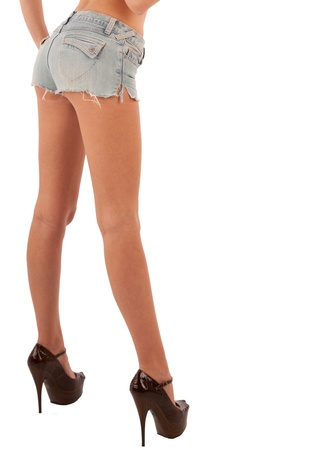 Studio shot of model with long legs and in high heels and denim shorts