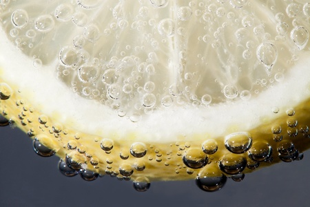 Slice of lemon in drink with bubbles Stock Photo