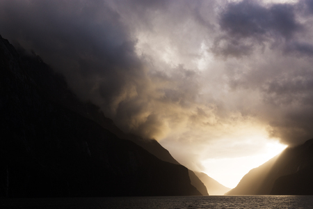 Bright sun light streams through ominous storm clouds as they hang over majestic snow capped peaks, lighting a layered path through the mountains.