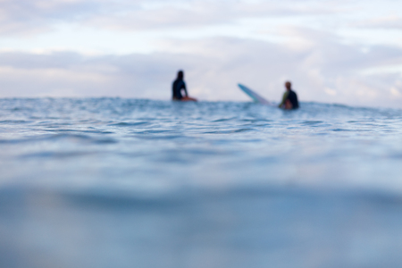 Two out of focus surfers sit in the distance on their surfboards as they wait for a wave to appear on the horizon.