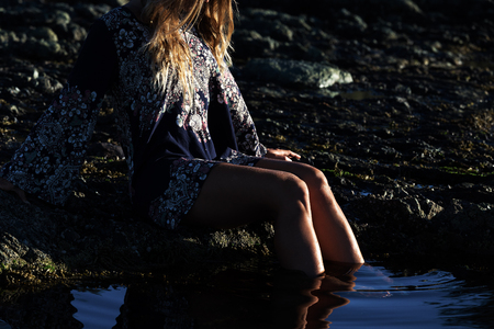 Stylish girl in dress sits by a rock pool at the beach.