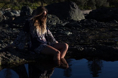 A stylish bohemian girl relaxes by a tidal rock pool at a scenic location in Australia. 版權商用圖片