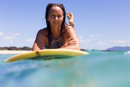 A portrait of a happy young surfer girl in pristine tropical water on a clear summers day in Australia.