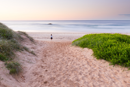 A single person stands at the end of footprint dotted walkway and watches a tranquil sunrise on the Australian coastline.