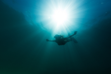 A young woman elegantly free dives into the depths of the Pacific Ocean as the sun illuminates the water around her. 版權商用圖片