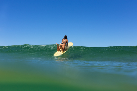 A beautiful young surfer girl in a bikini paddles over a clear ocean wave beneath a blue summer sky.