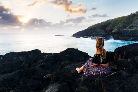 A beautiful bohemian-styled girl sits on a rocky headland and watches the morning sun burst above the clouds during a magnificent sunrise in Australia.
