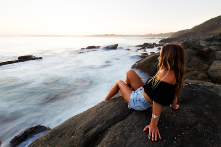 A healthy, tanned young woman sits on a boulder and watches the summer sun set over a beautiful seascape in Australia. Stock Photo