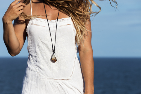 A young, bohemian woman wearing a white dress and a crystal necklace holds her hair as it blows in the sea breeze by the ocean.