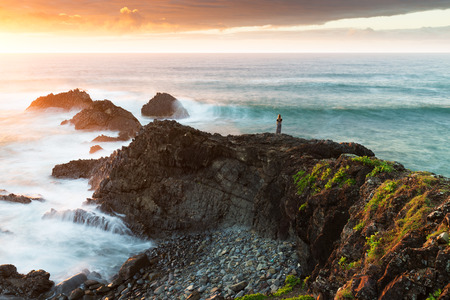 A woman is dwarfed in a majestic coastal scene as the sun rises and highlights the vibrant colours of the landscape and crashing waves.