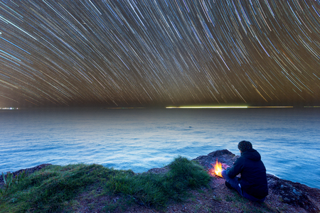 A hiker sitting on top of a high cliff above the Pacific Ocean warms his hands over a camp fire as the stars shine bright in the night sky.