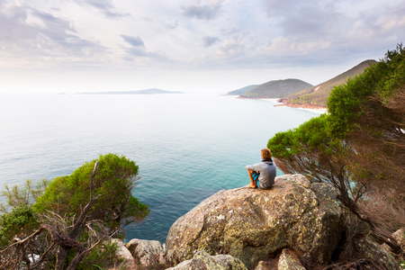 A man sits on a boulder overlooking a panoramic view of a beautiful ocean coastline near Newcastle, Australia.