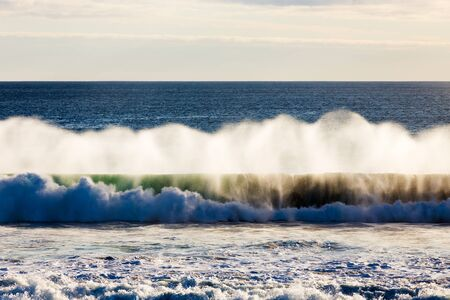 A powerful Southern Ocean wave crashes into shore, as the spray is illuminated in soft evening light on an isolated beach in South Australia.